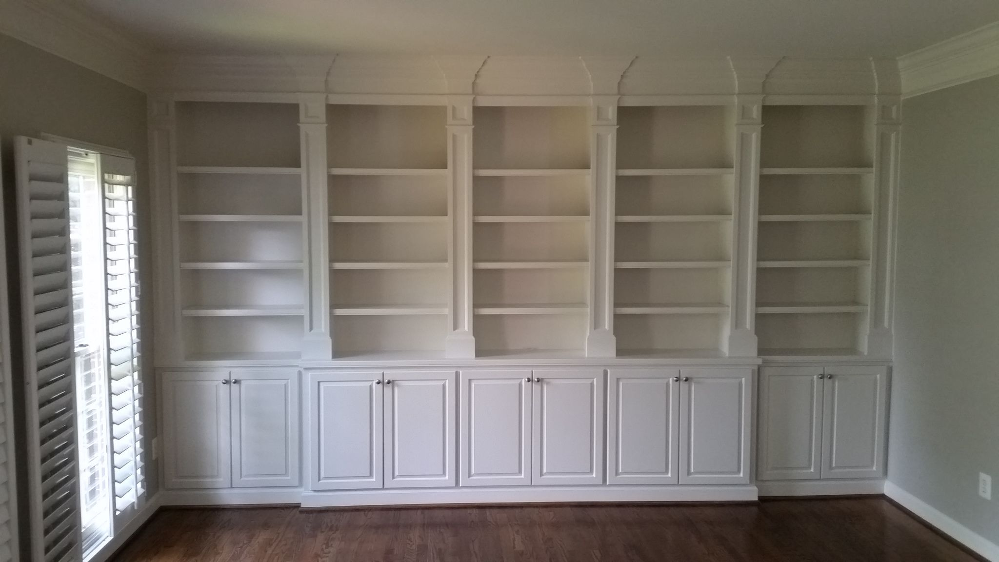 White Built In Cabinetry Featuring Recessed Pilaster Stiles, Adjustable Shelving, And