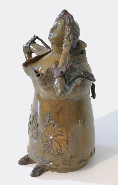 A remarkable redware flask in the form of a woman wearing a long gown with a very open ruffled bodice that leaves little to the imagination. Folksy, somewhat risque and definitely unique, this unusual figure is difficult to date or place but is probably late eighteenth or early nineteenth century and is either Continental or from the American south where it was part of a collection. An amazing suvivor with only two or three minor chips.