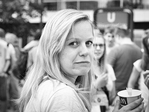 Candid Portrait einer jungen Frau mit einem Trinkbecher von McDonalds in der Hand.
