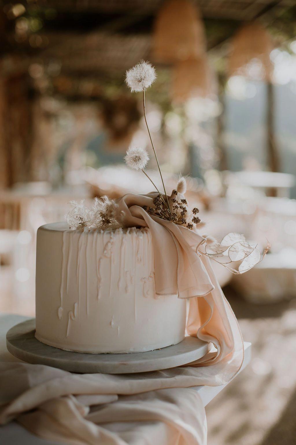 Modern minimal delicate wedding drip cake with dried