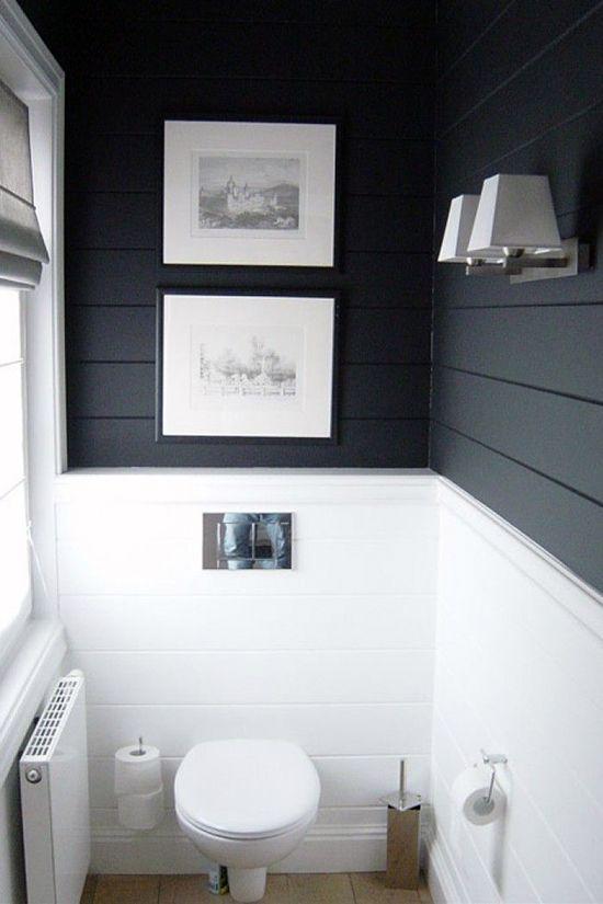 Petite powder room with dark walls above wainscoting of white subway