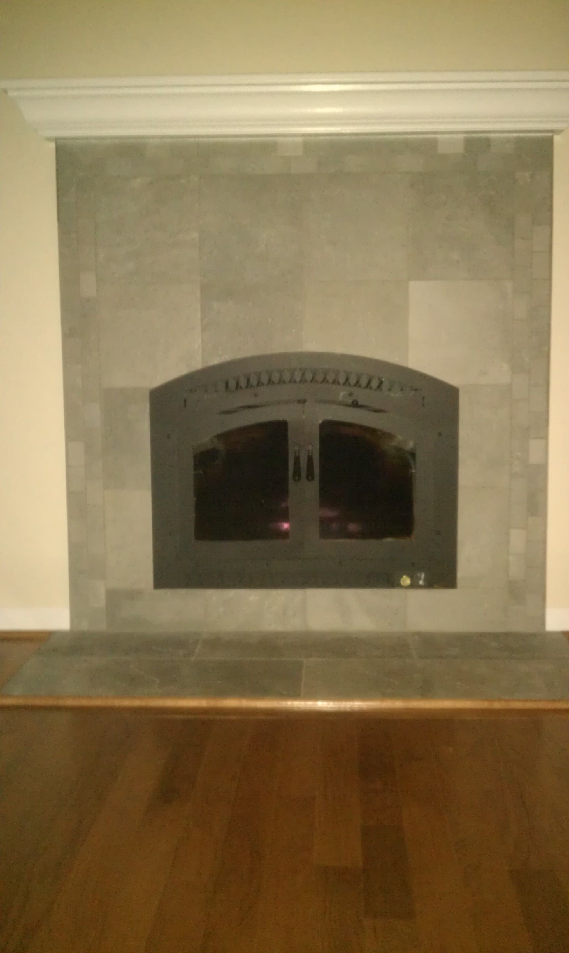 custom mantle and fireplace surround this wood burning stove http