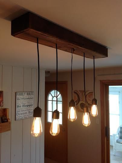 this light fixture was created with used pallet wood to create the box with hanging edison