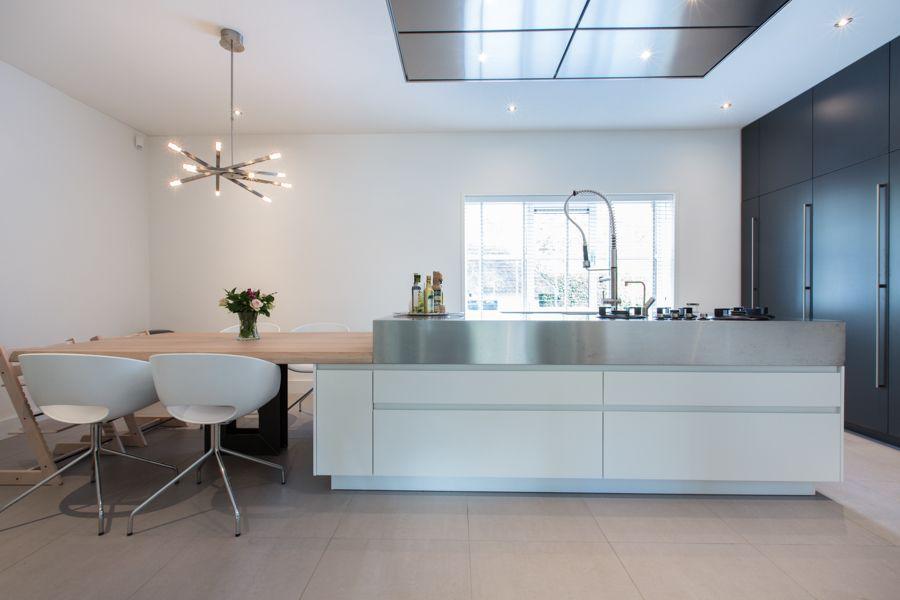 Kook-/ spoeleiland met extra dik RVS werkblad doorlopend in eettafel met robuste eiken blad.   Kastenwand van vloer tot plafond in contasterende houtkleur — in Helmond.