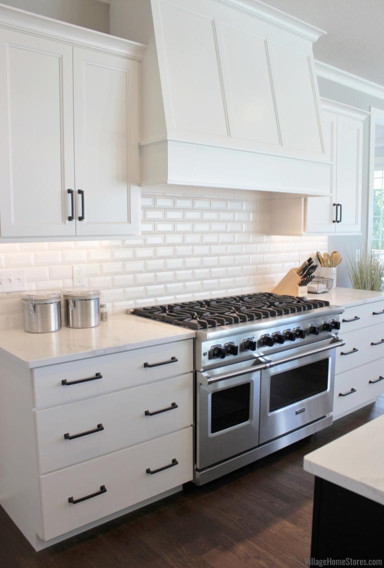 White cabinet kitchen with wood range hood and Viking range ...