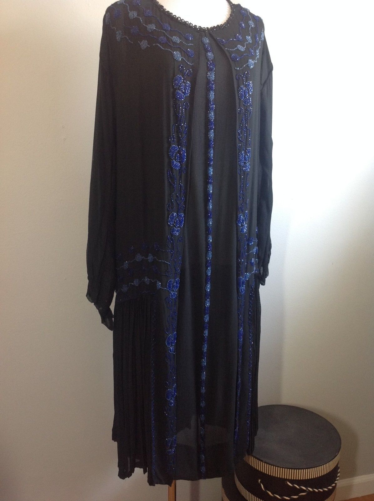 1920s Beaded Silk Flapper Dress Blue Floral Art Deco.  Beaded in light and dark blue glass beads with a pansy design.  The beading flaps at the front and back as well as the pleated bottom are separate from the under dress and swing when moving. Front