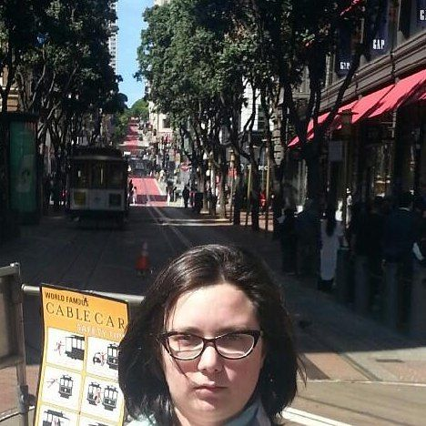 This is me giving my best tourist face waiting in line for our return trolley. by landetravel