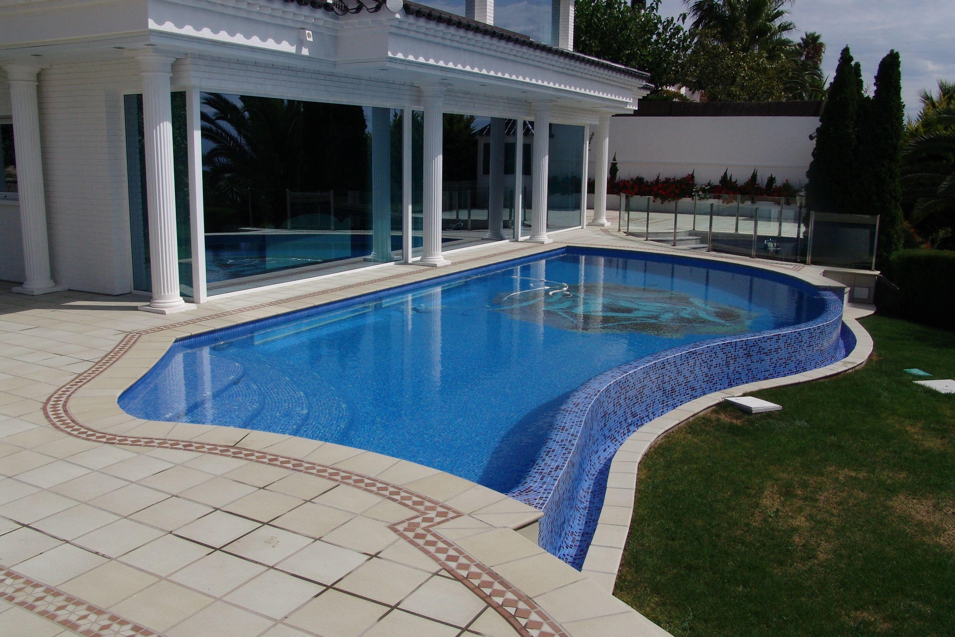 Piscina de FERRÓN®PISCINAS. Enorme piscina de diseño desbordante con escalera de obra de acceso interior.