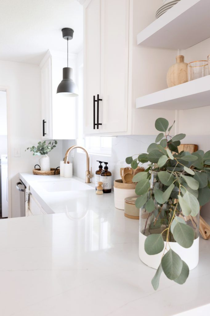 modern and minimal home decor inspiration | simple white kitchen with industrial accents, gold details, and green plants
