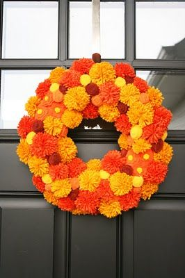 Fall wreath with yarn pompoms, fleece roses, and felt flowers. Maybe try this in winter colors of white and blue and purple?