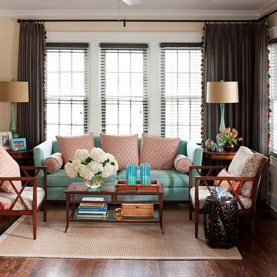 Cool Down  To make a statement, throw a cool fabric into a mix of warm ones. In this rosy room, the teal sofa is a breath of fresh air among the rich wood floors and pink pillows. Slender blue lamps and candleholders help to integrate the colors.