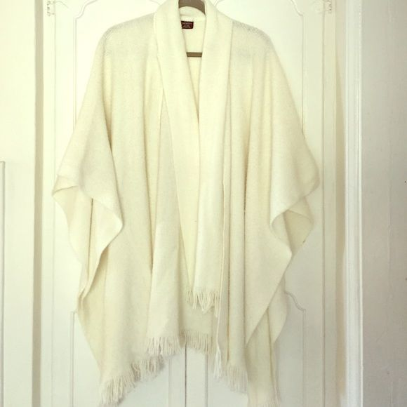 Cream cozy poncho Cream knit poncho has a self knit tie.  Can be tie close to the next or draped down to give variety to the wearer!  100% acrylic, fringe trim, has some piling as pictured.  Length from center back to back hem is 34.5in Sweaters Shrugs & Ponchos