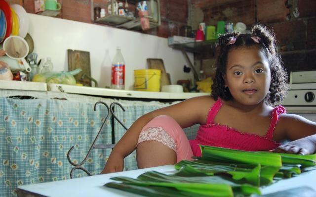 Foto de niña con síndrome de Down ayudando en la cocina