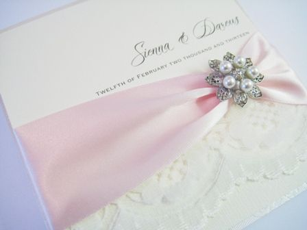 wedding invitation with pink satin ribbon lace and brooch detail