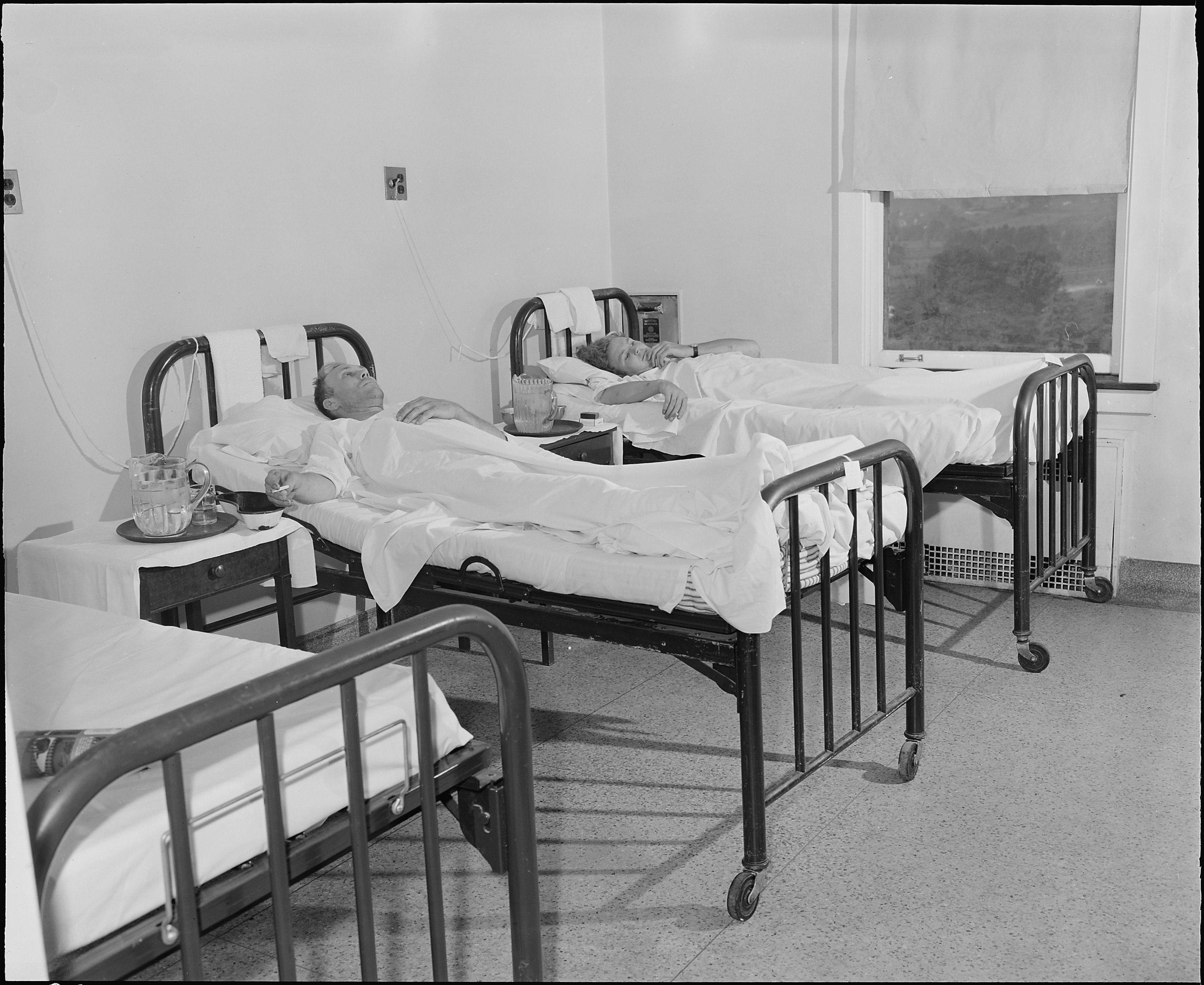 Black and white photo of two patients laying in hospital