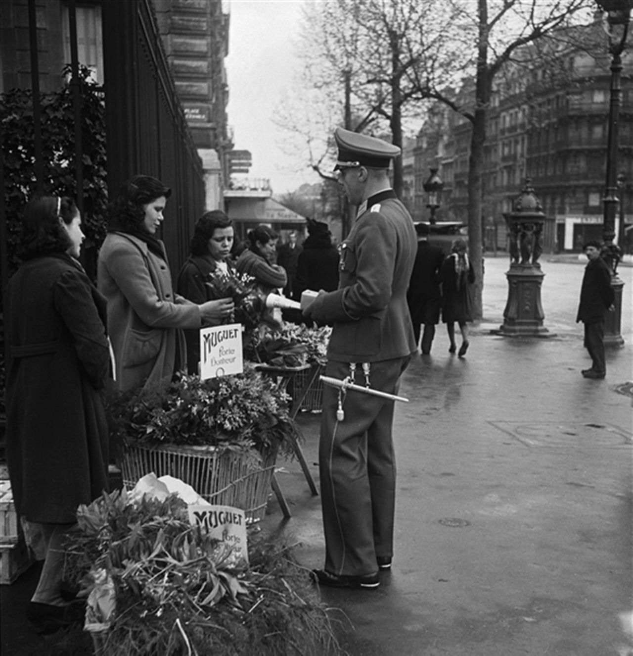 A german officer buying a bouquet featuring lily of the valley a german officer buying a bouquet featuring lily of the valley muguet in paris france on 1 may 1941 the day when the french greet each other with a m4hsunfo