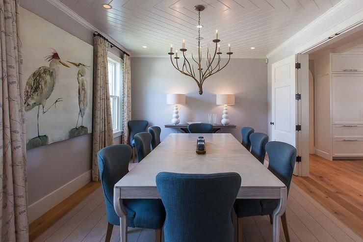 Contemporary Dining Room Boasts A Shiplap Geometric Ceiling Accented With Faux Branch Chandelier Hanging Over Gray Table Lined Blue Wingback