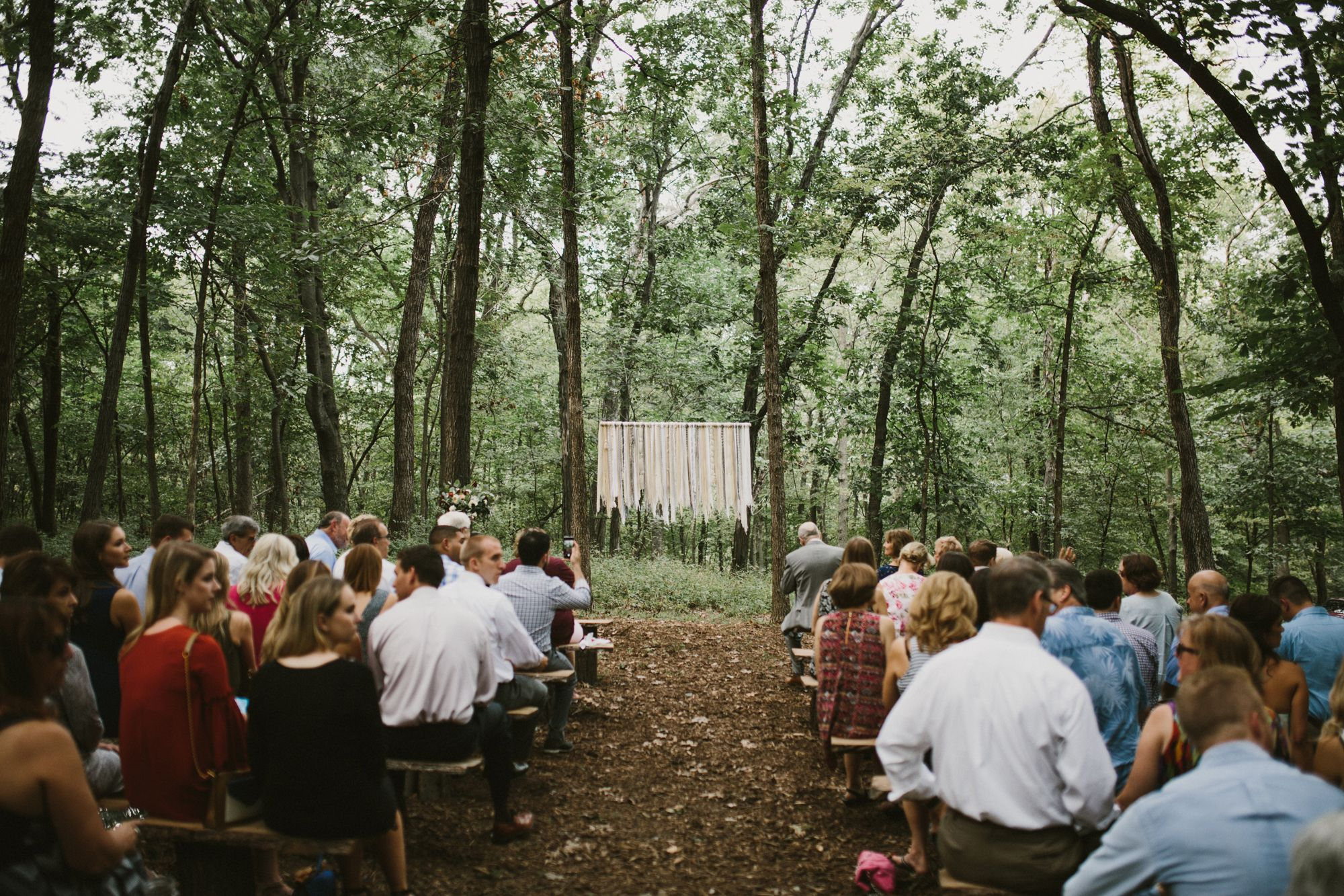 diy backyard wedding in the woods ceremony space wooden benches