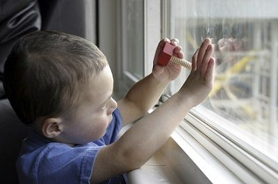 child with hands on closed window