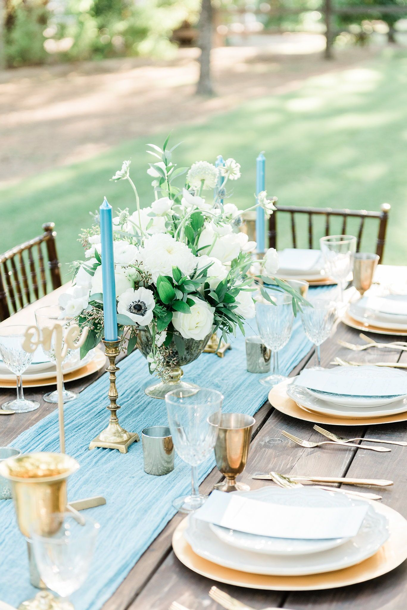 Reception Table Centerpiece Featuring Greenery And Anemone
