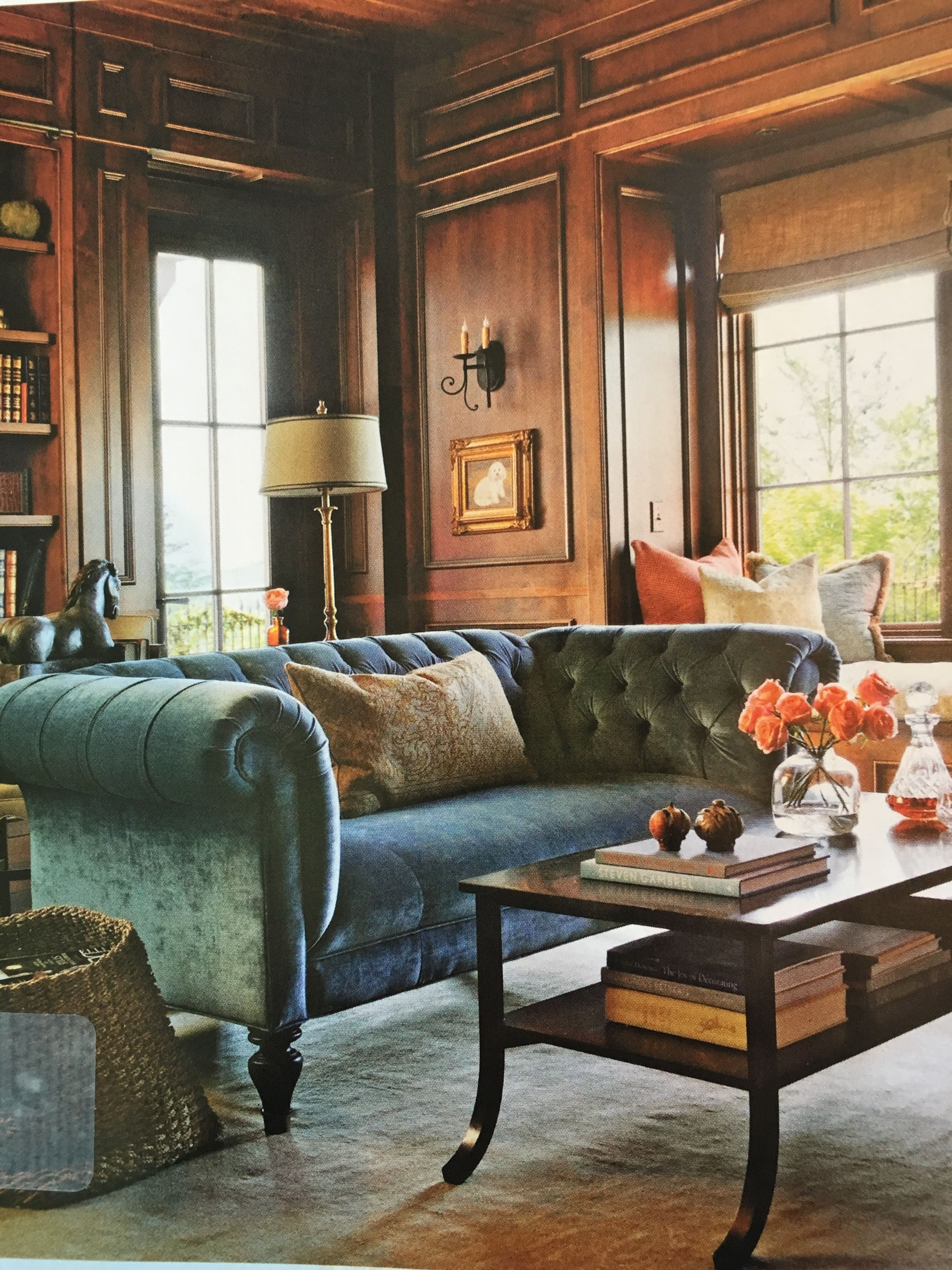 Love the warm blue sofa with gold accents on wall mixed in