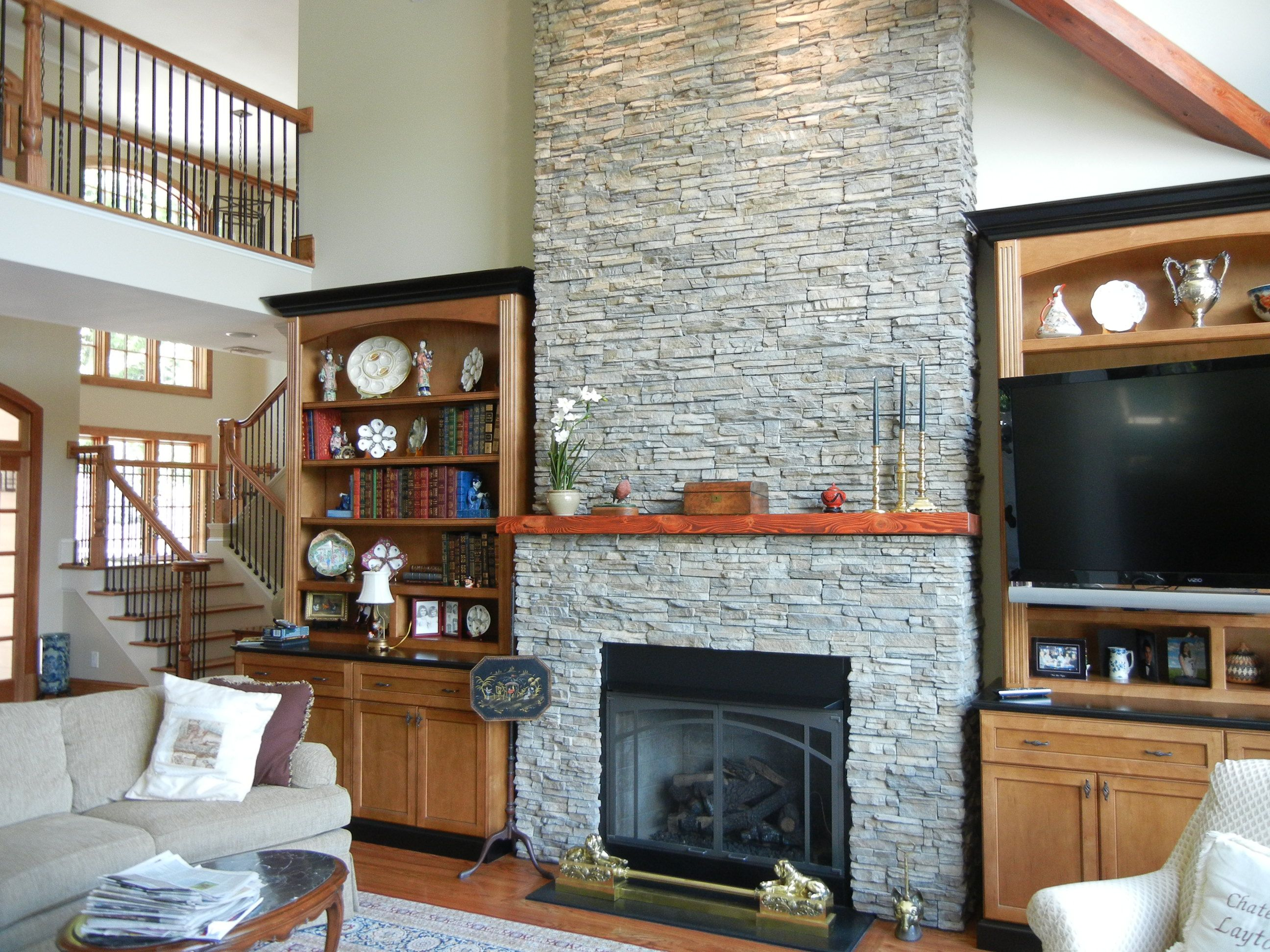 stone fireplace surrounded by built in bookshelves creates a lovely