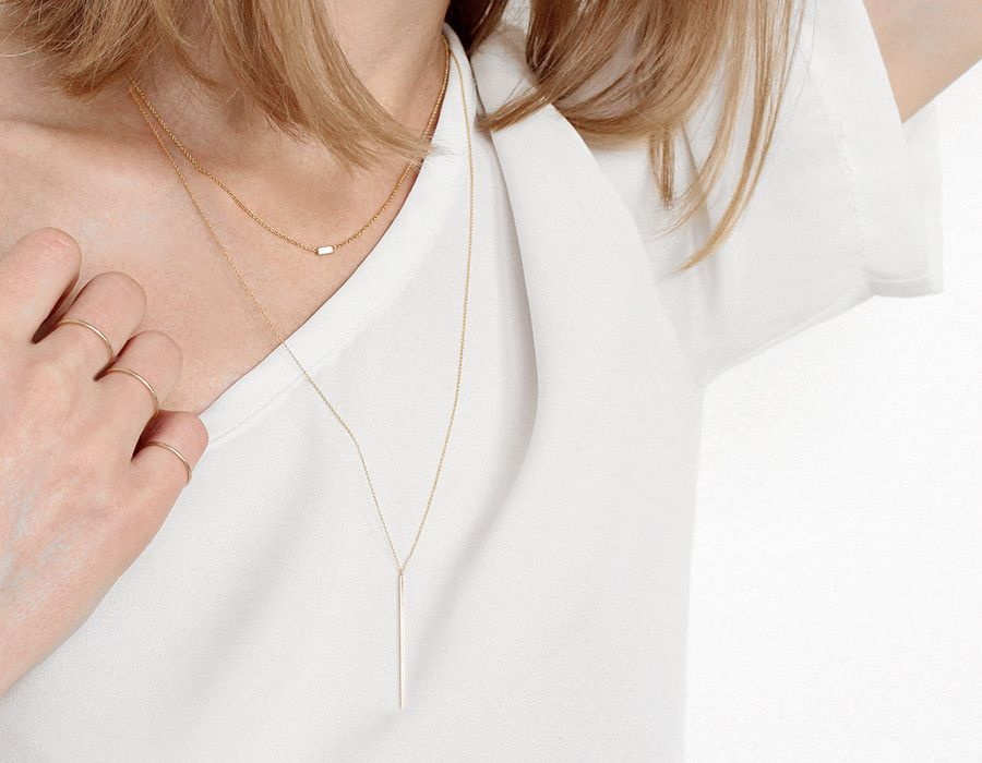Pre-Release (short run of 30 available) This dainty necklace features a solid 14k gold bar, hangingvertically on a thin gold chain. Its adjustable length makes it a perfect necklace to layer(as shown with the baguette necklace), and can also add elegance to any outfit on its own. • 14k solid...