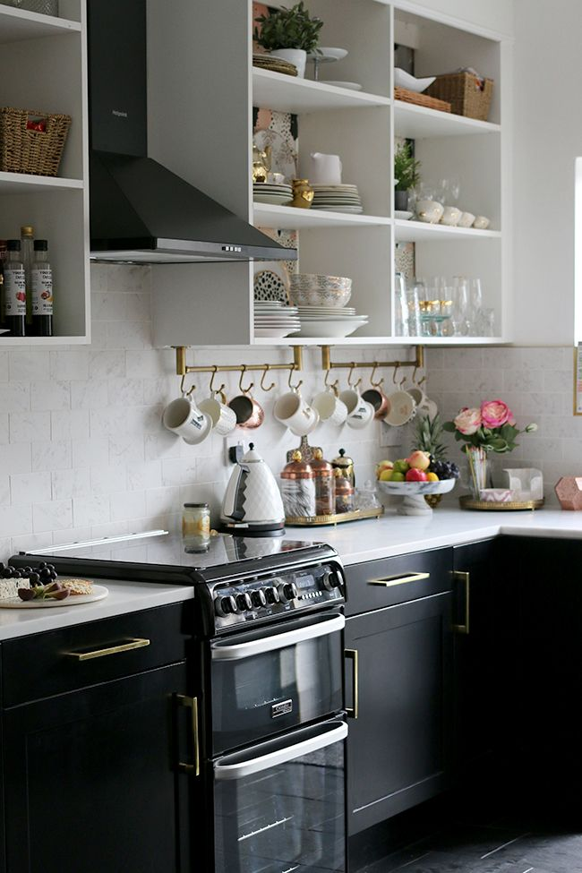 kitchen with black cupboards with white open shelving marble tiles and brass accents - white kitchen shelves