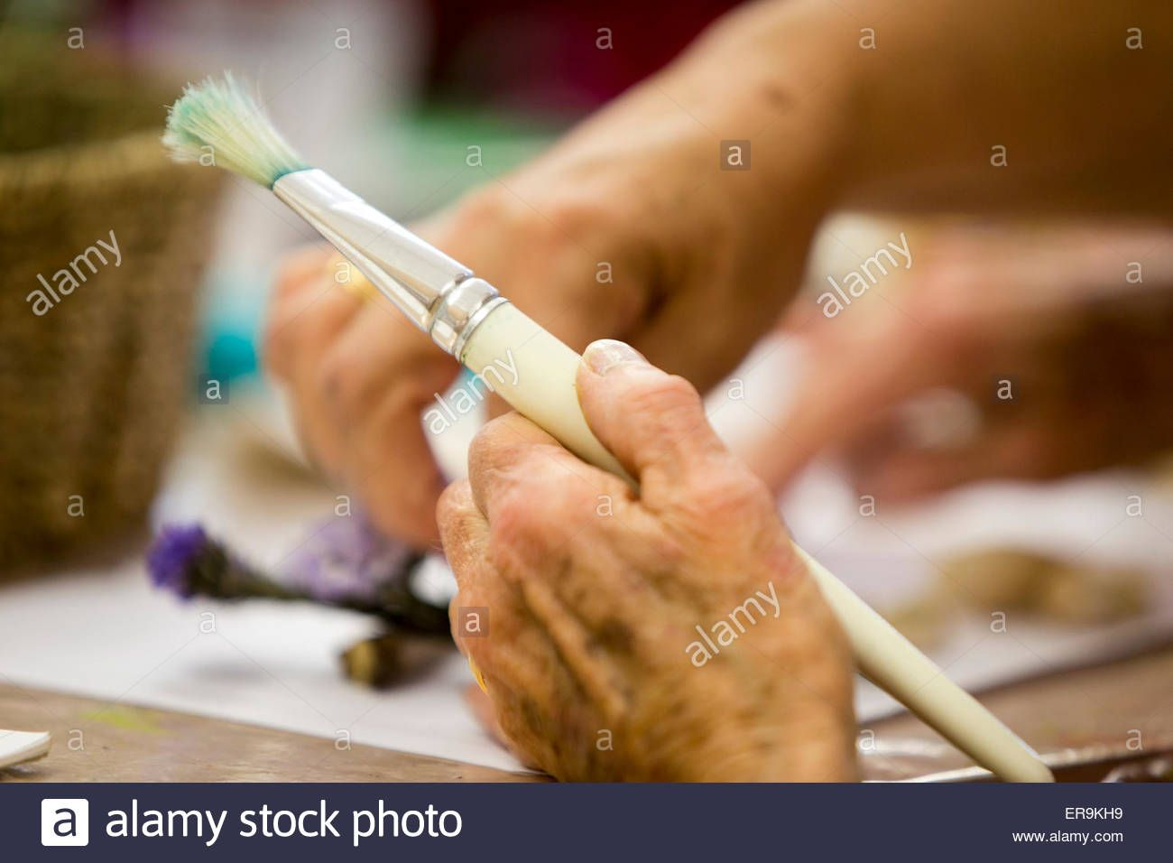 An elderly woman s hand holds a paint brush Stock