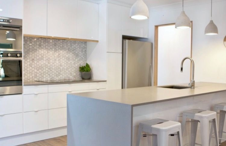 Sleek concrete bench top, white cupboards, marble tiles ...