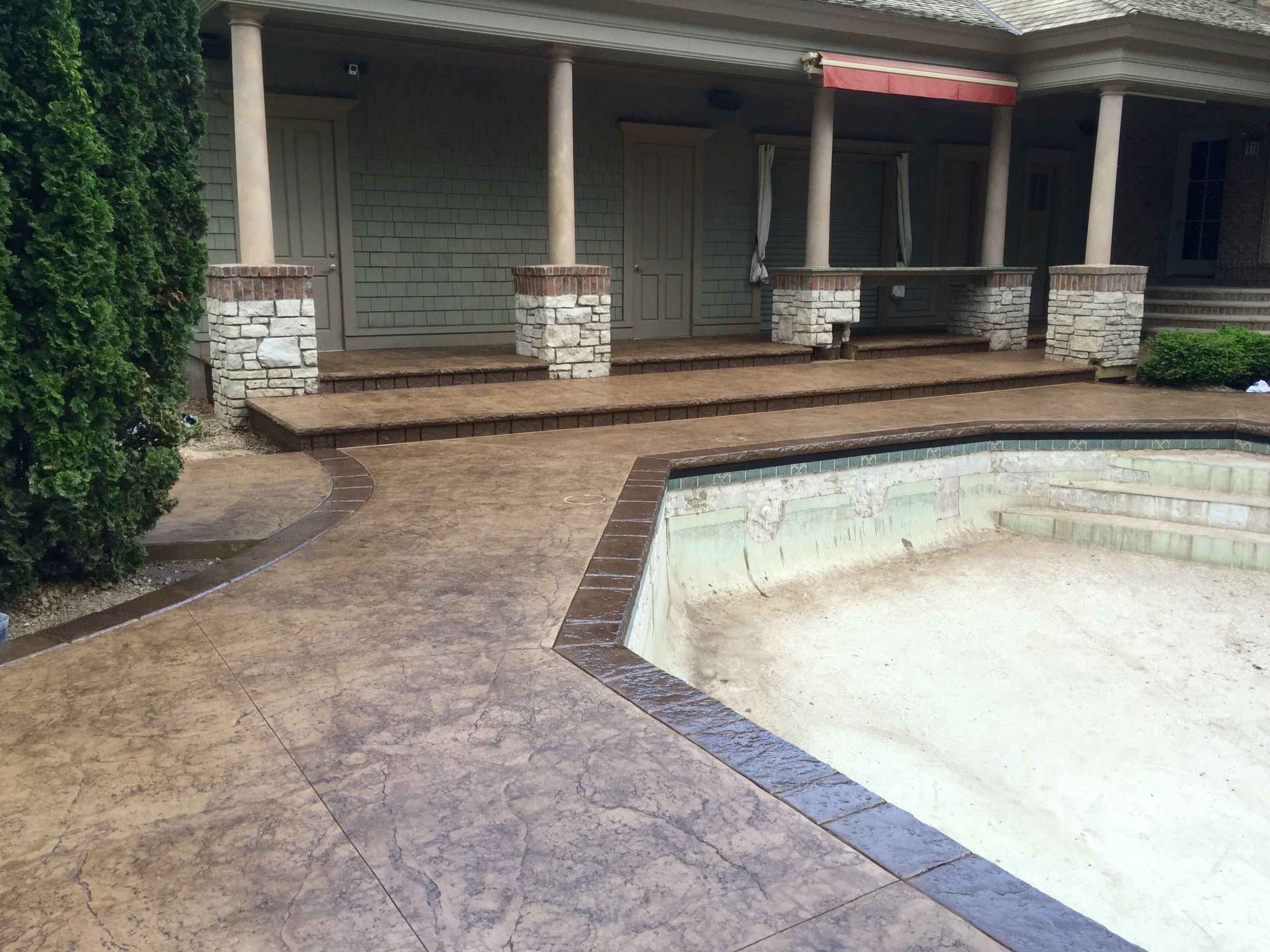 stamped concrete pool deck with custom chiseled stone cantilevered
