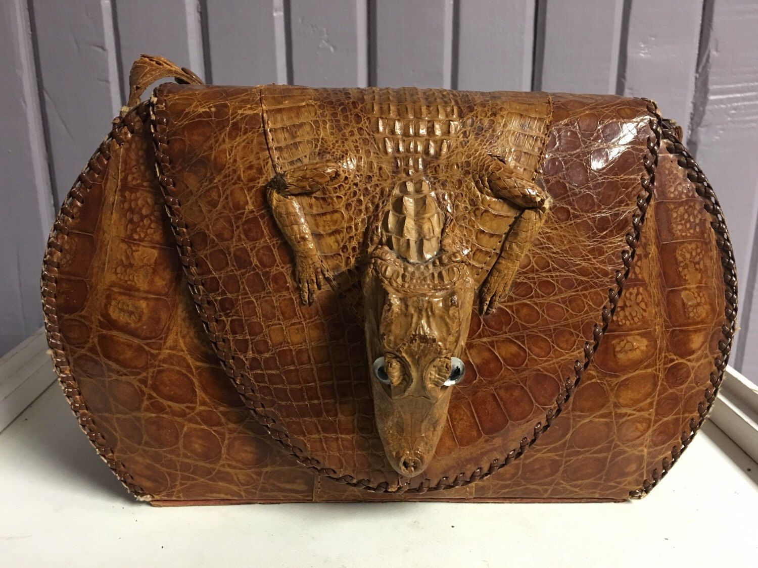 A personal favorite from my Etsy shop https://www.etsy.com/listing/270833083/genuine-alligator-handbag-with-head-and