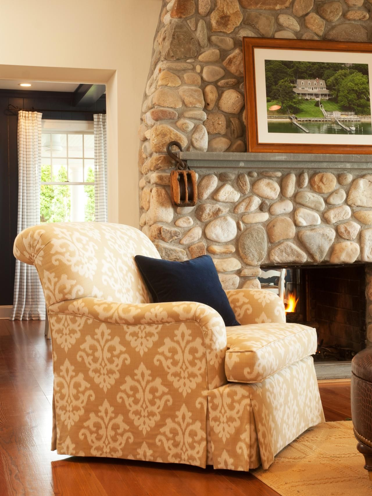 A natural stone fireplace and patterned tan patterned armchair set
