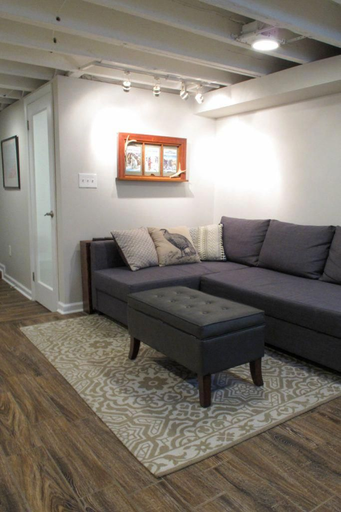 Photo of Cozy Chic Basement Reno with Exposed Painted Joists & Wood Tile Floors