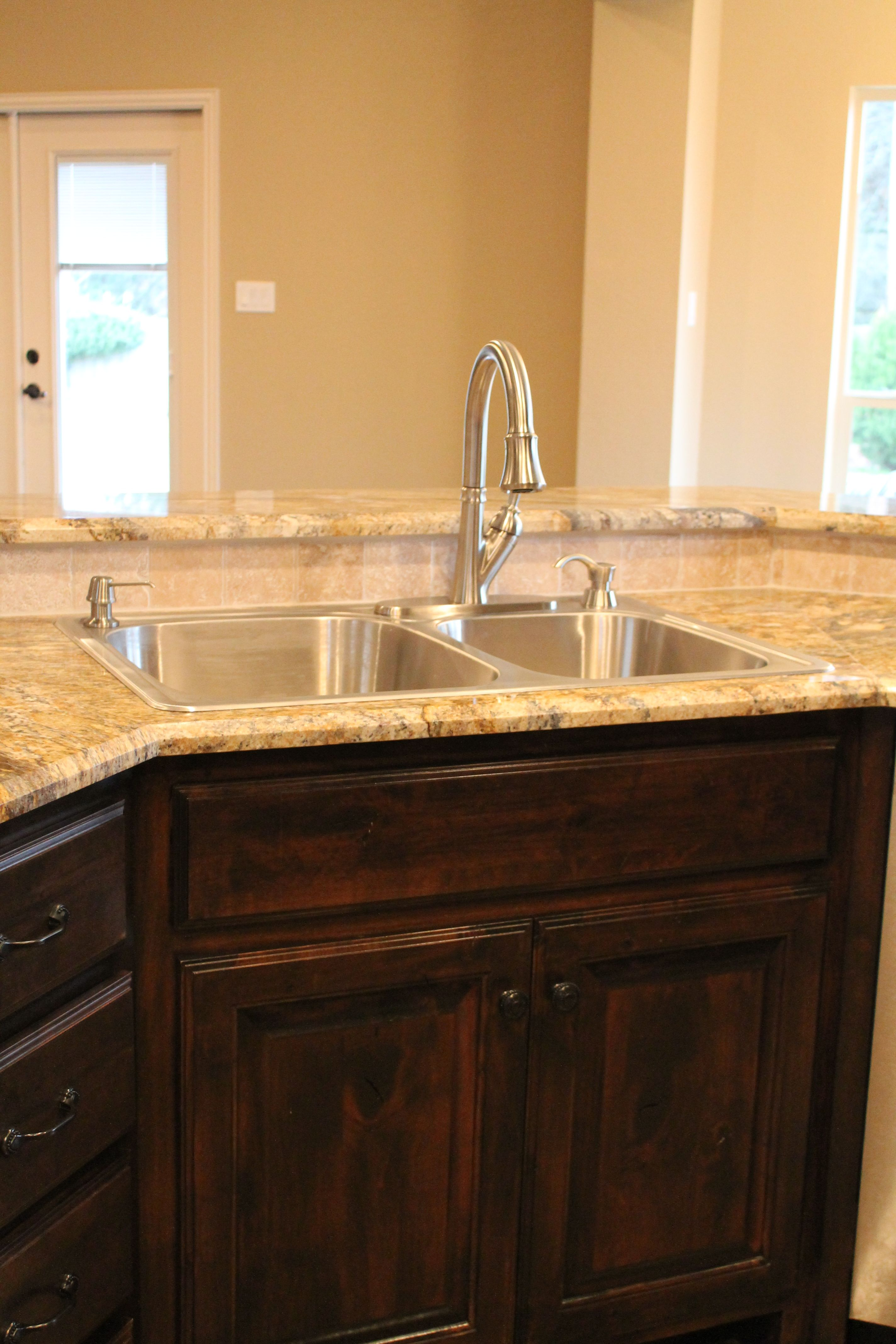 Custom kitchen with stainless steel appliances granite countertop tumbled stone backsplash tile stained