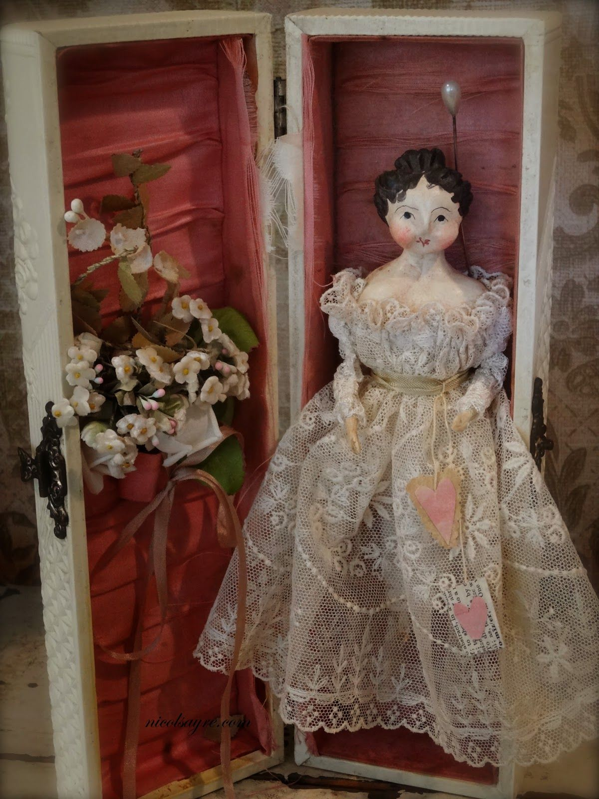 """Nicol Sayre Doll Shoppe,,Fleur is a tiny little thing at 7"""" dress all in antique lace. She is papier mache on a cloth body and is pinned into a wonderful 11"""" vintage celluloid box embossed with roses and lined with shredded silk. She carries her valentines and a vintage little posy in her box"""
