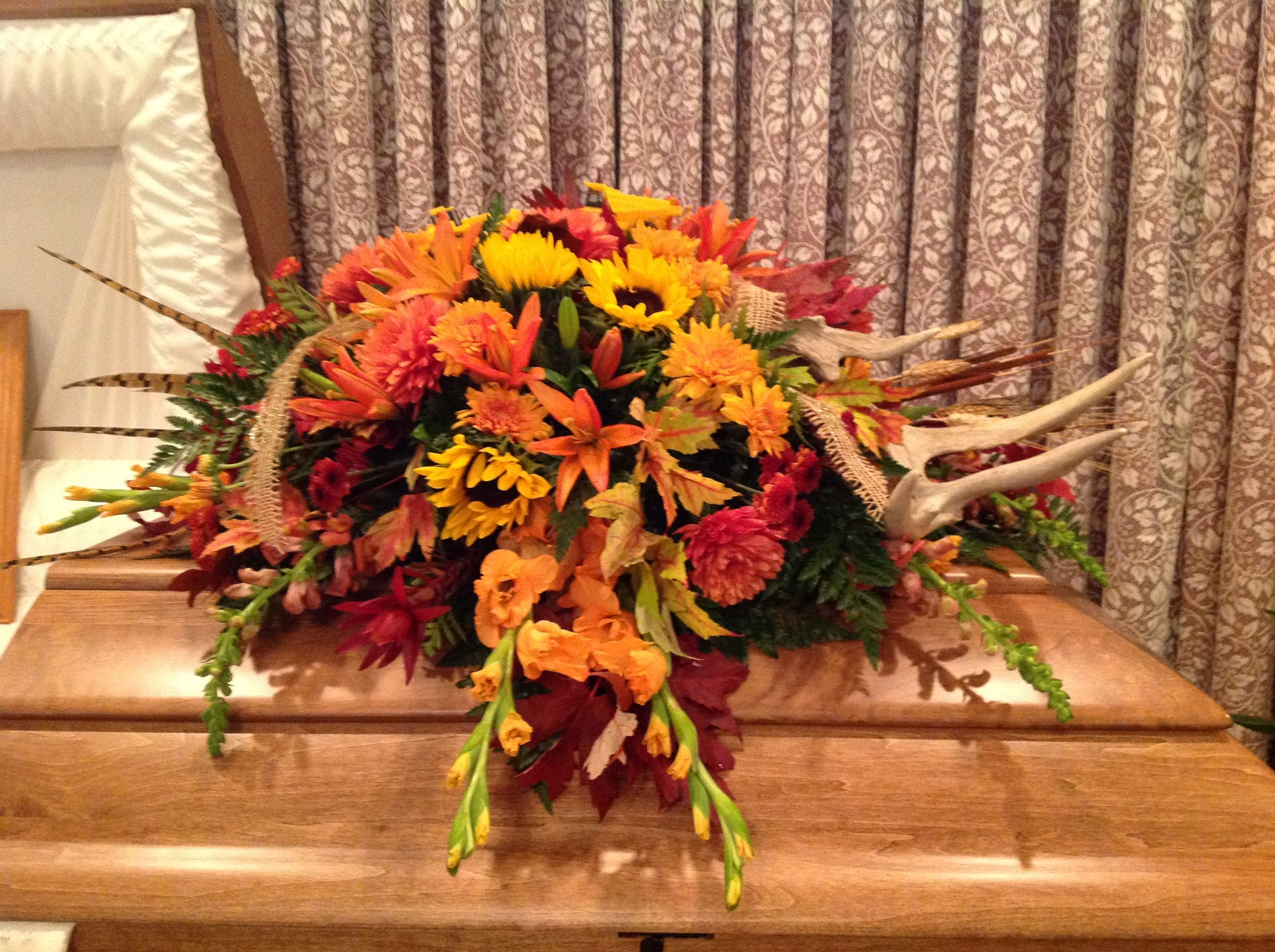 Casket spray of fall flowers and leaves along with pheasant feathers wheat