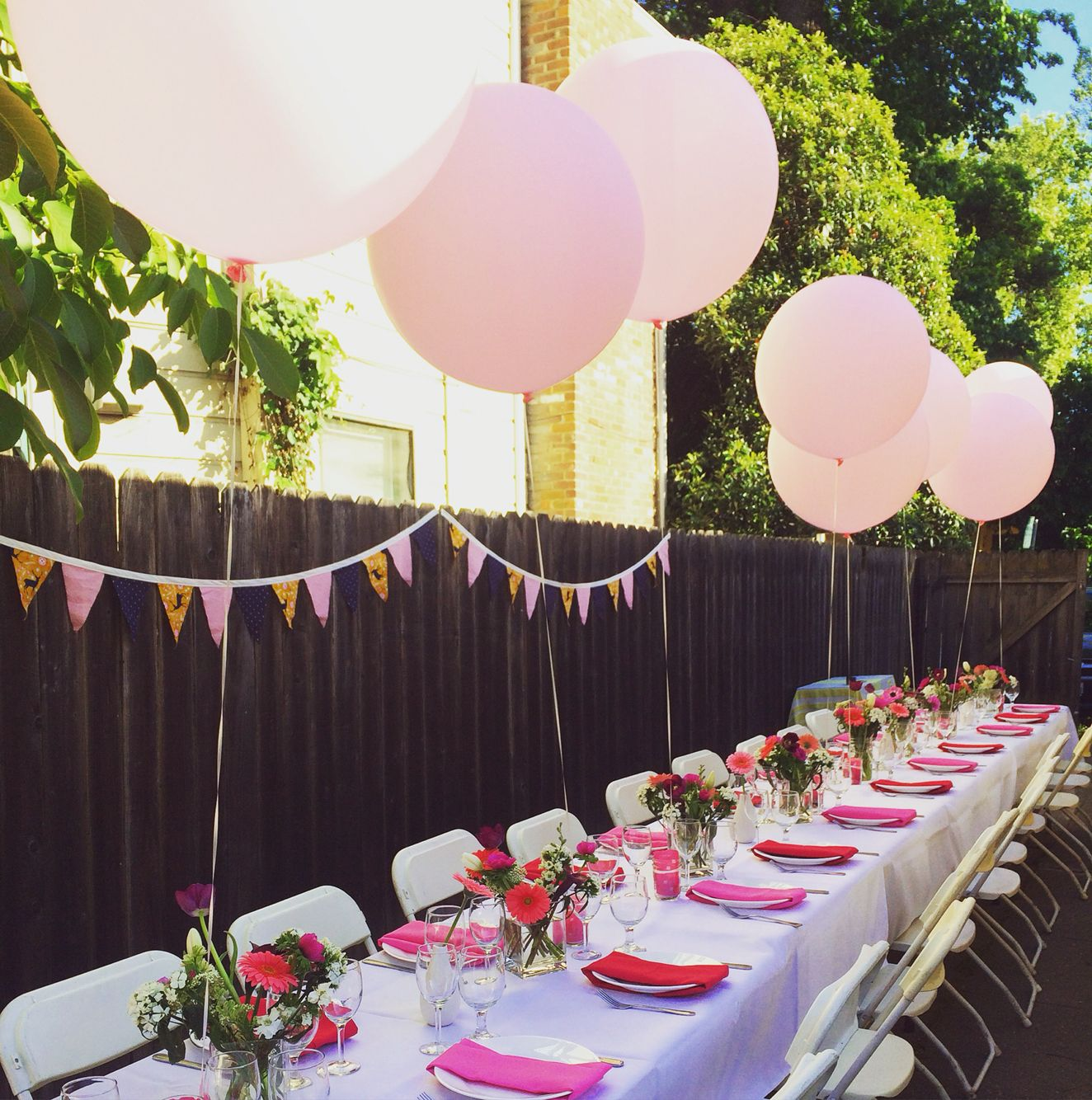 Backyard party with pink oversized balloons