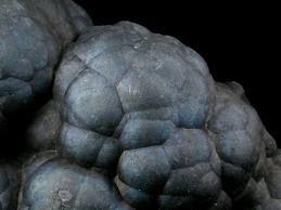 Romanèchite.Colour:Greyish black, black. Hardness:5 - 6 .Named after its discovery locality, Romanèche, Saône-et-Loir, France.