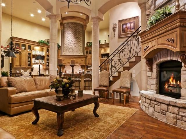Corner kitchen behind living room with corner fireplace and arches dream home pinterest for Living rooms with corner fireplaces