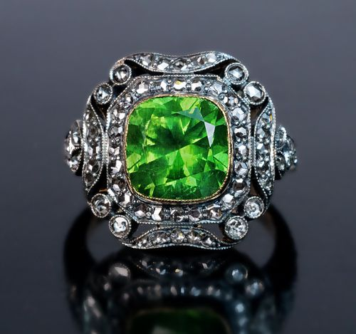 A Rare Russian Demantoid, Diamond, Silver and Gold Art Deco Engagement Ring, Circa 1930s. This 14K gold ring features a 4.19 ct vivid green Russian demantoid set in an ornate silver over gold frame embellished with numerous rose cut diamonds.