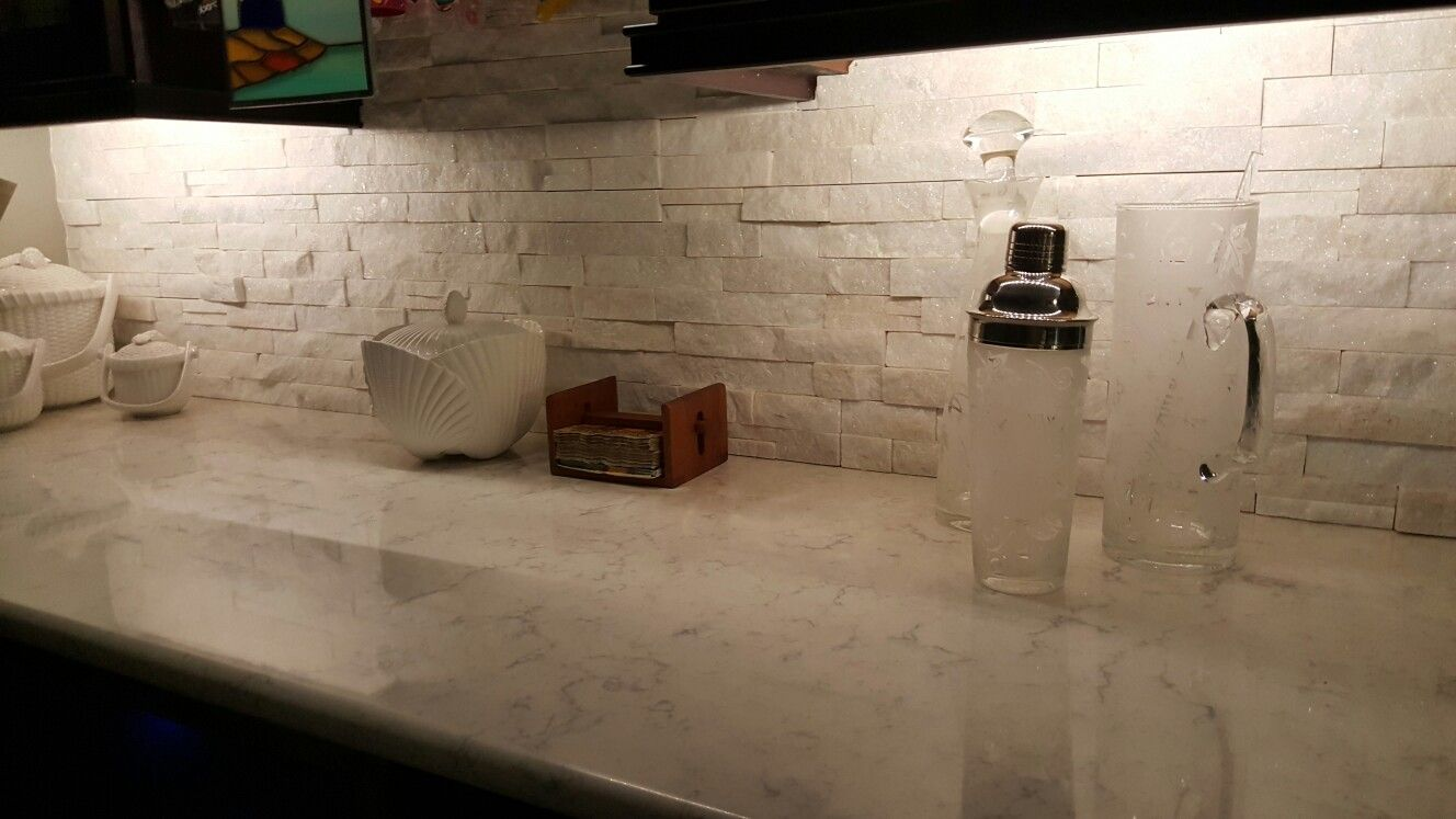 Sparkling white stacked Stone backsplash on Carrera quartz counter ...