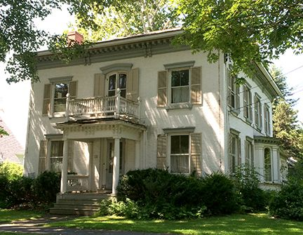 A massive brick dwelling featuring paired corbels interspersed with smaller brackets, and a  charming walk-out second floor porch. The bay window with roundheads, and  Classical touches creeping in on the frieze and porch columns.  We always think of Italianate as a Victorian style, which it is, but don't forget its origins in Classicism.