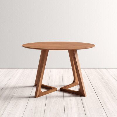 null Laid-back enough for takeout on a Friday but classy enough for wine and a cheese board on a Saturday – this dining table is a win-win. Made from solid walnut wood, this circular tabletop has a beveled edge for a clean look. The two geometric sled-like legs nearly touch at the base to create an X shape for interesting visual appeal. Its natural wood finish is a great look no matter the style of your dining room. This table measures 47