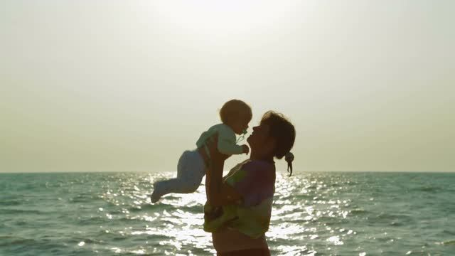 waist-down-shot-of-a-happy-mother-playing-with-her-baby-boy-at-the-seaside-throwing-him-up-and-embracing-shot-is-made-in-crimea-at-the-black-sea-with-small-waves-the-sun-is-reflected-on-water_voxliexkyl__M0000.jpg (640×360)