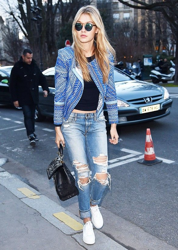 Gigi Hadid wears a black crop top with distressed boyfriend jeans, a blue printed jacket, structured black bag and circle sunglasses.