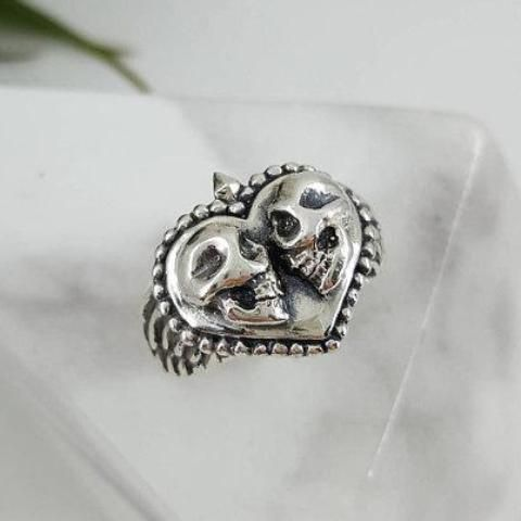 """Eternal Love Skull Ring in Sterling Silver: Features two very detailed skulls gazing into each other's vacant eye-holes. Sculpted wings adorn each side of the heart, framing it. Very """"out of the ordinary"""" gift for the one you love. Back of band is 3mm.The band on this ring could be made thicker to accommodate mens sizes as well. Contact me for inquiries.(The ring shown is a size 7) Due to the handmade nature of our items, please allow 2-3 weeks for production."""