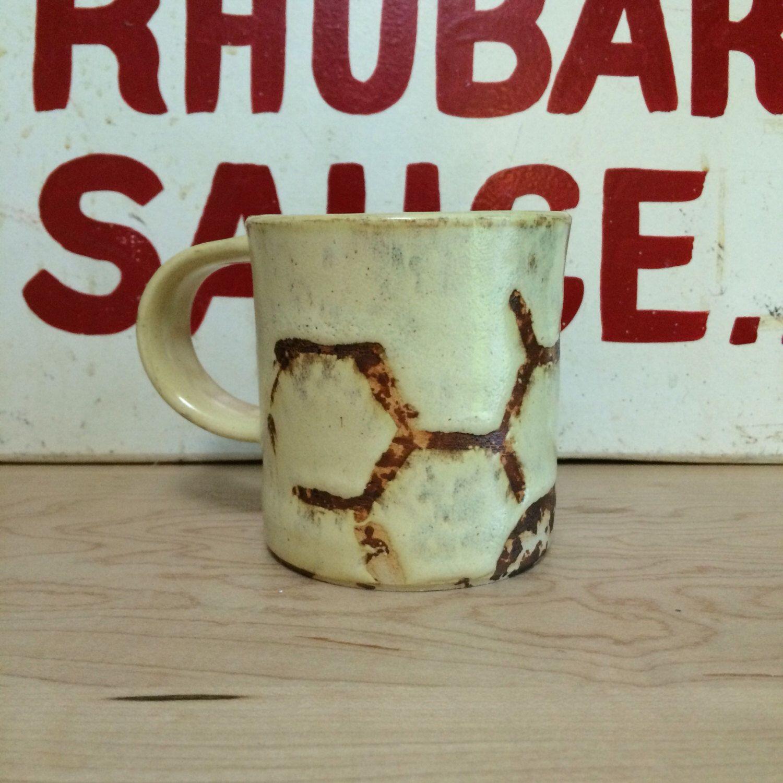 A yellow ceramic coffee or tea mug, with a yellow