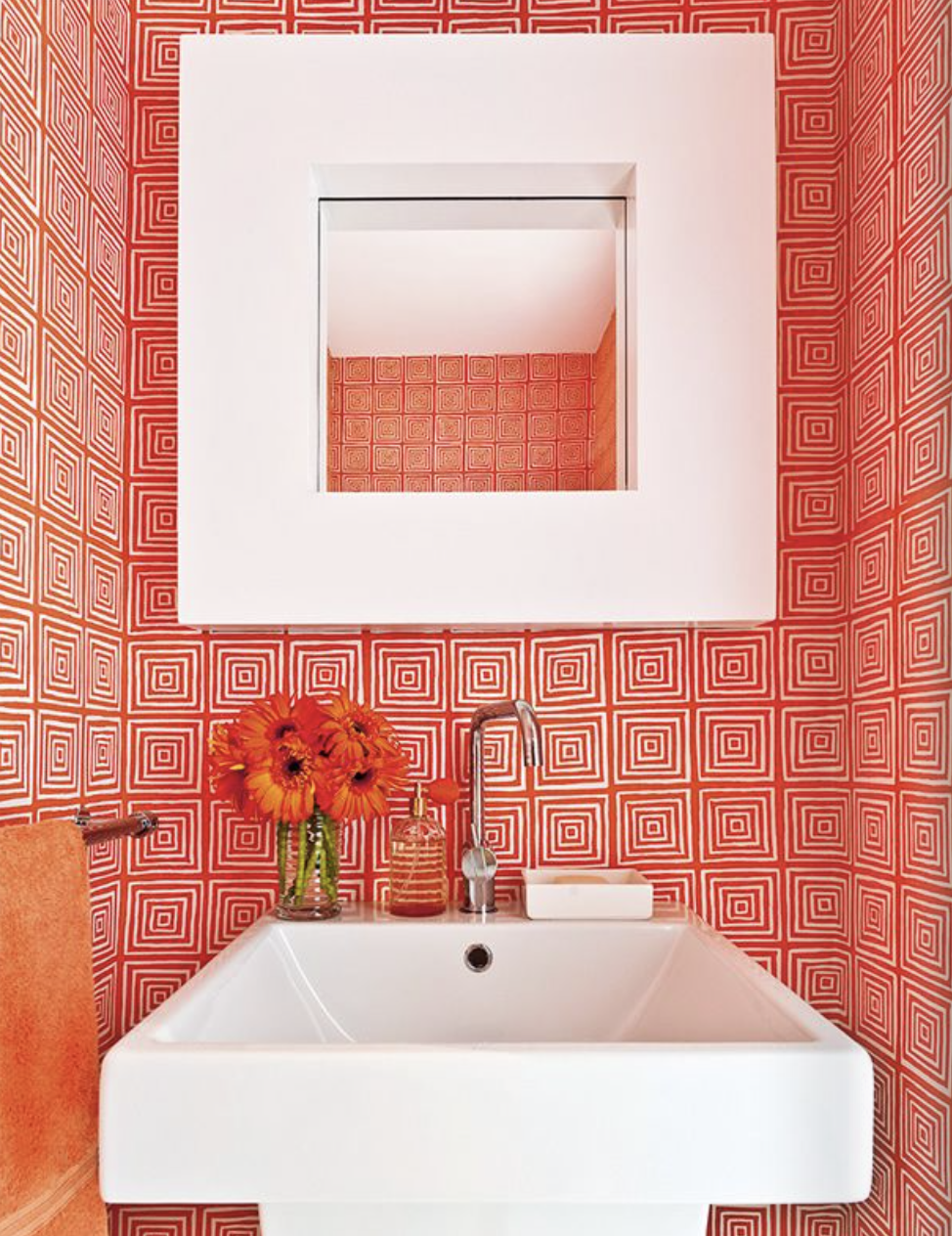 This bathroom is so cool looking with this bright orange