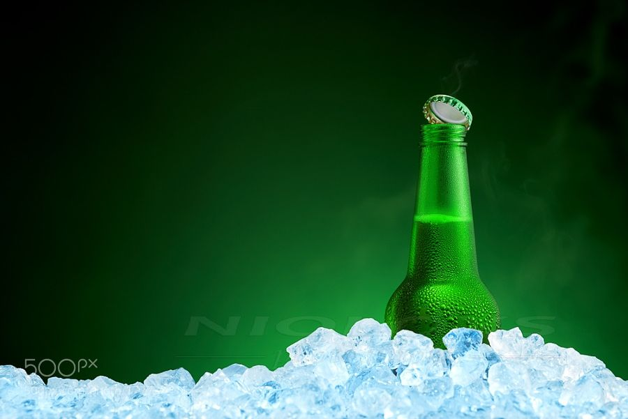 Bottle of cold beer in ice on green background by nioloxs